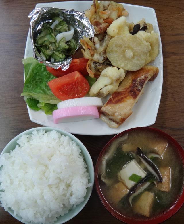 株式会社日食 今日のお昼ごはん ごはん 味噌汁 ぶりの塩焼き 天ぷら イカときゅうりの酢の物 かまぼこ レタス トマト